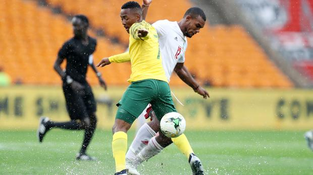 Lebohang Maboe battles for possession with Perry Monnaie of Seychelles at a drenched FNB Stadium on Saturday. Photo: Muzi Ntombela/BackpagePix